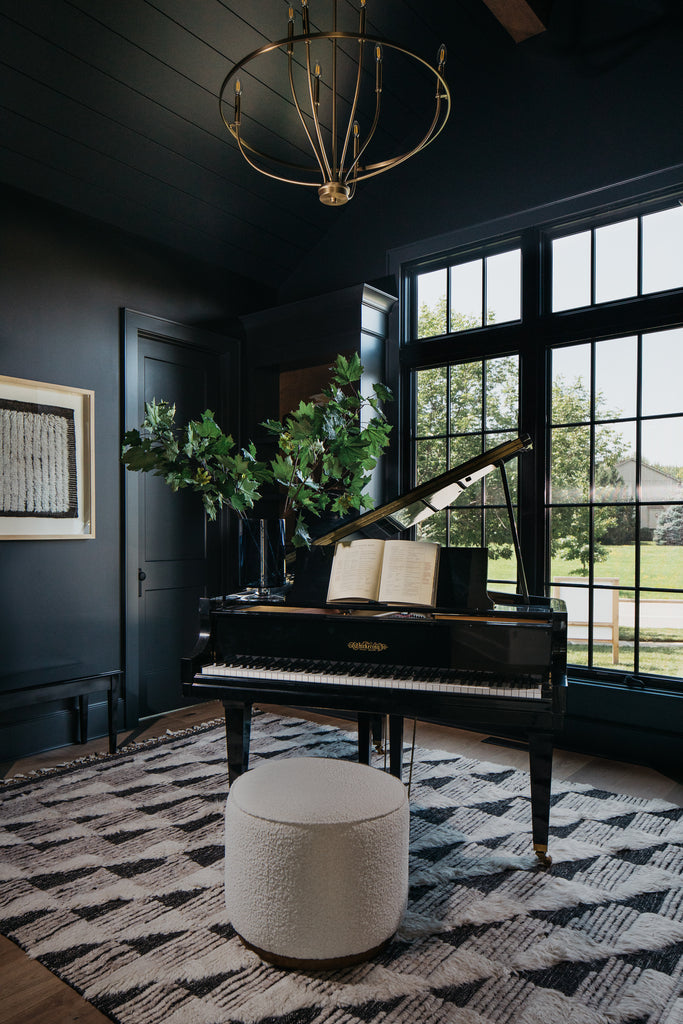 Moody piano music study with dark green walls, Moroccan rug, and black windows.