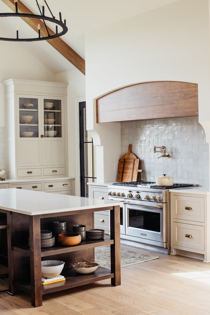 Vaulted ceiling in kitchen with beige cabinetry, wood stained island with quartz, zellige tile backsplash.