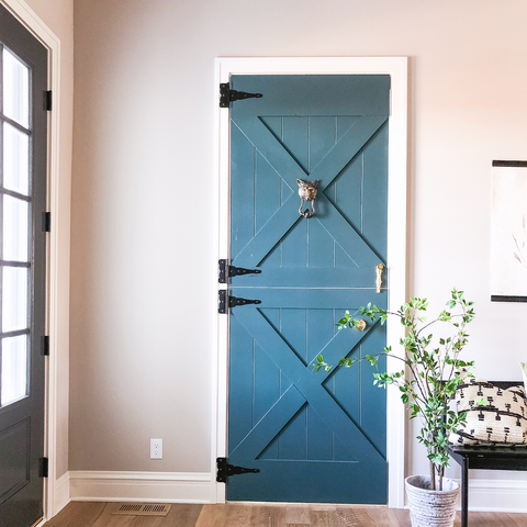A blue statement dutch door leading to the office right off the entry.  Black wood bench designed by Ben Petersen.