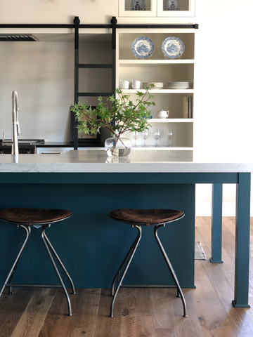 Blue statement island with quartz paired with leather counterstools.  Open shelving storage in the kitchen perfect for stacking dishes.  Minimalist kitchen vibes. Kitchen ladder for hard to reach cabinets!
