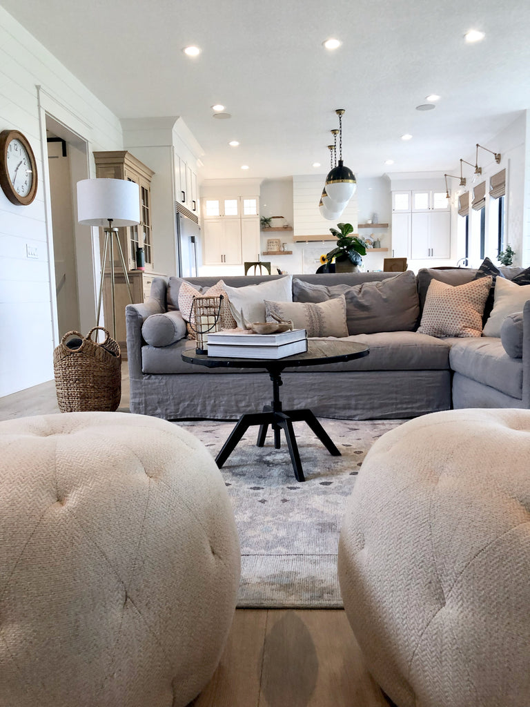 Dalia sectional slipcovered in grey linen by Cisco Brothers in this midwest modern farmhouse near Ames, IA.  Kai wool rug by Jaipur in beautiful grey medallion pattern paired with a cognac leather Emmett sling chair by Four Hands.  All white kitchen with warm white oak wood floors by Joelle Elaine Design.