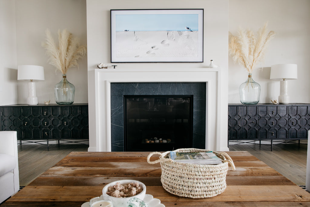 We love the client's selection of bluestone for the fireplace flanked with white molding. The precious black Dovetail cabinets, creamy white pampas grass in recycled glass vases, and white hand-glazed ceramic Tory lamps from Arteriors give the living room a warm and beachy vibe.