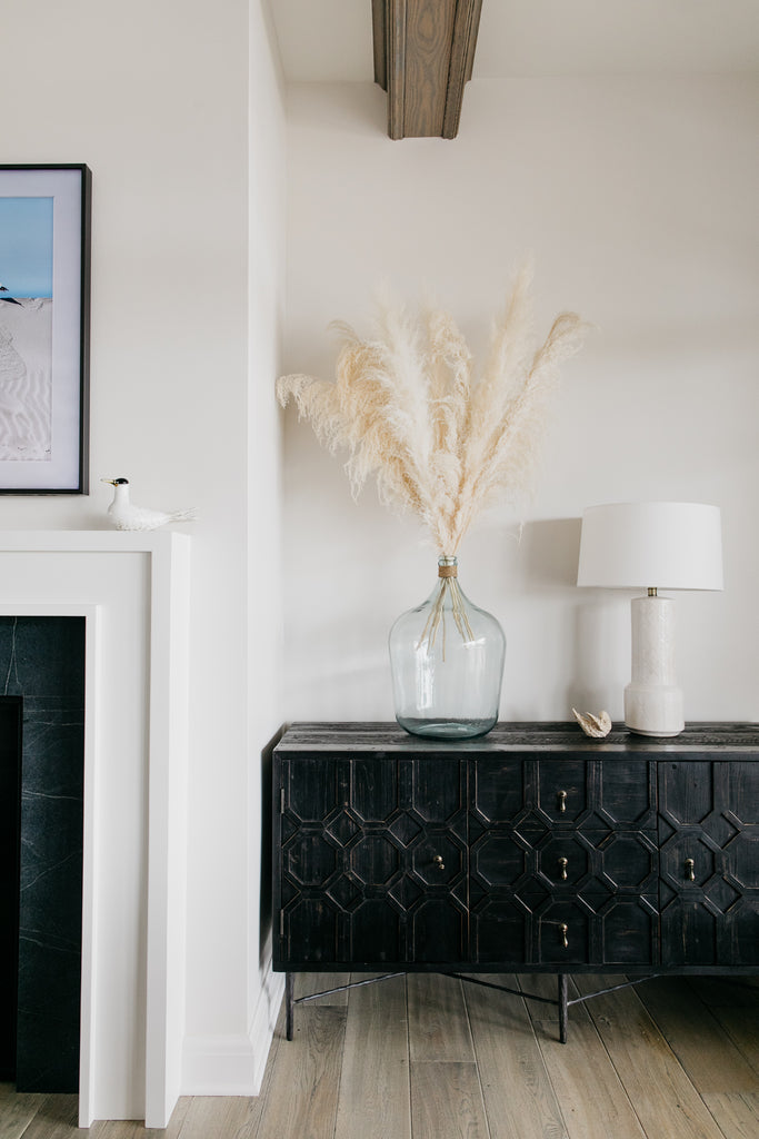 The precious black Dovetail cabinets, creamy white pampas grass in recycled glass vases, and white hand-glazed ceramic Tory lamps from Arteriors give the living room a warm and beachy vibe.