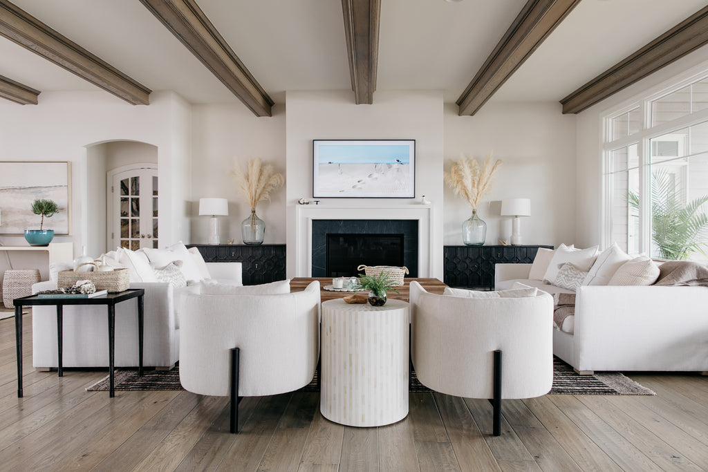 The Verellen Sullivan chairs and Thibaut sofas are a star of the show in crisp white linen in this modern coastal lakehouse in Omaha, Nebraska designed by Amethyst Home.