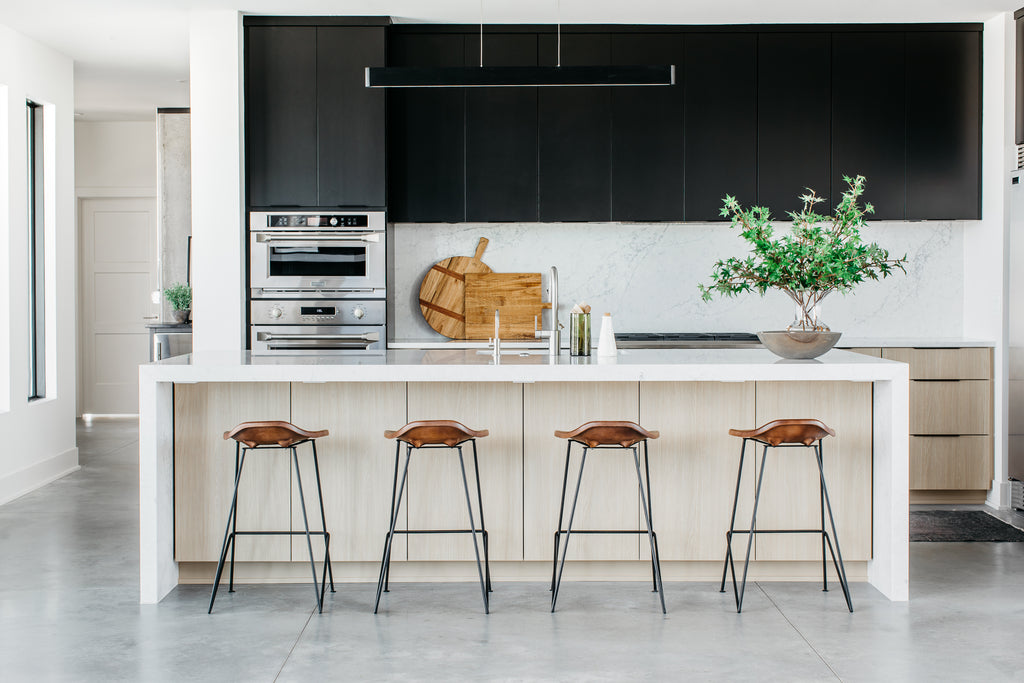 A bright and airy kitchen with sleek white quartz counters, steel appliances and bold black cabinetry.