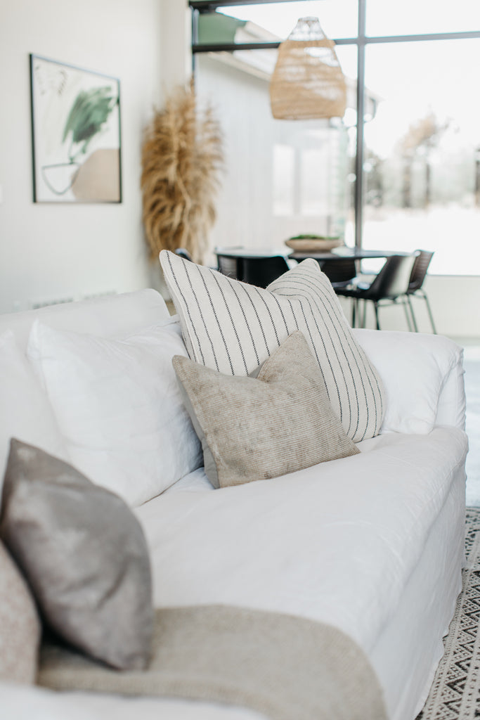 Beautiful, one-of-a-kind pillows adorn a white Cisco Brothers Donato Sofa.