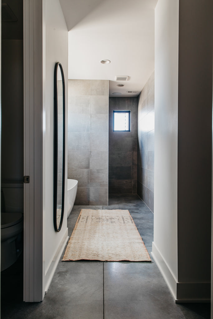 Spa-like master bathroom featuring an oval-shaped iron mirror, sandy rug and white tub.