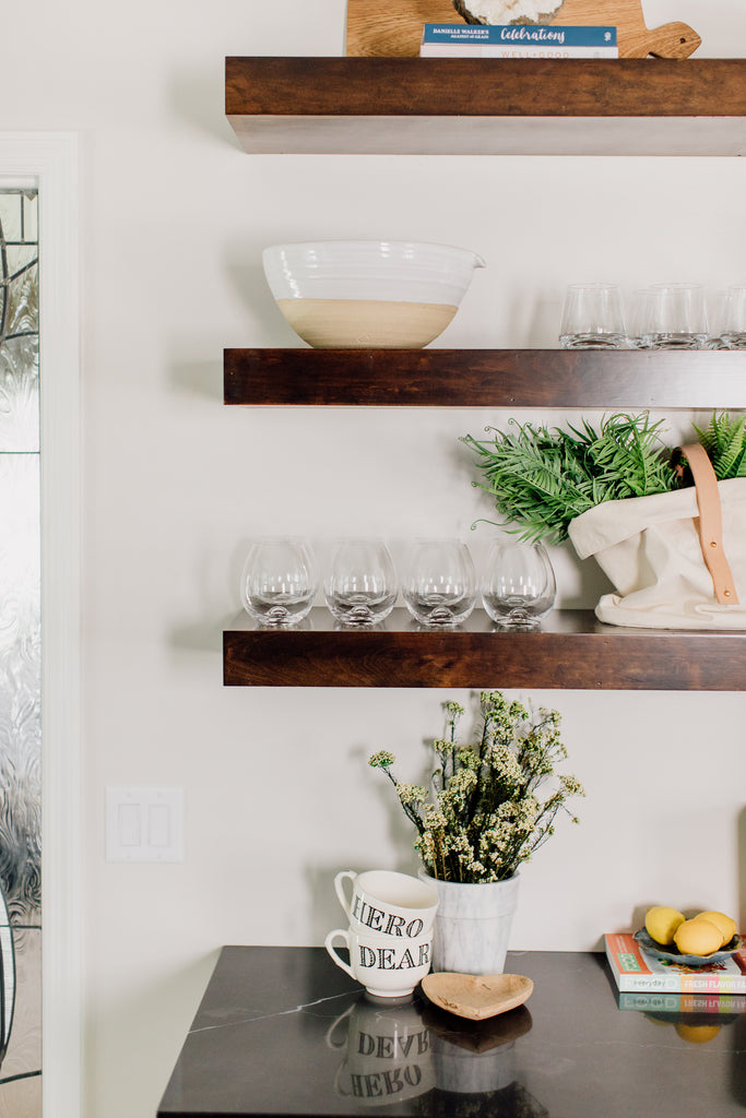 The custom-built open shelving in the kitchen is such a fun contrast to the cabinets. This is such a gorgeous way to show off cute ceramic and glassware along with seasonal decor and flowers.