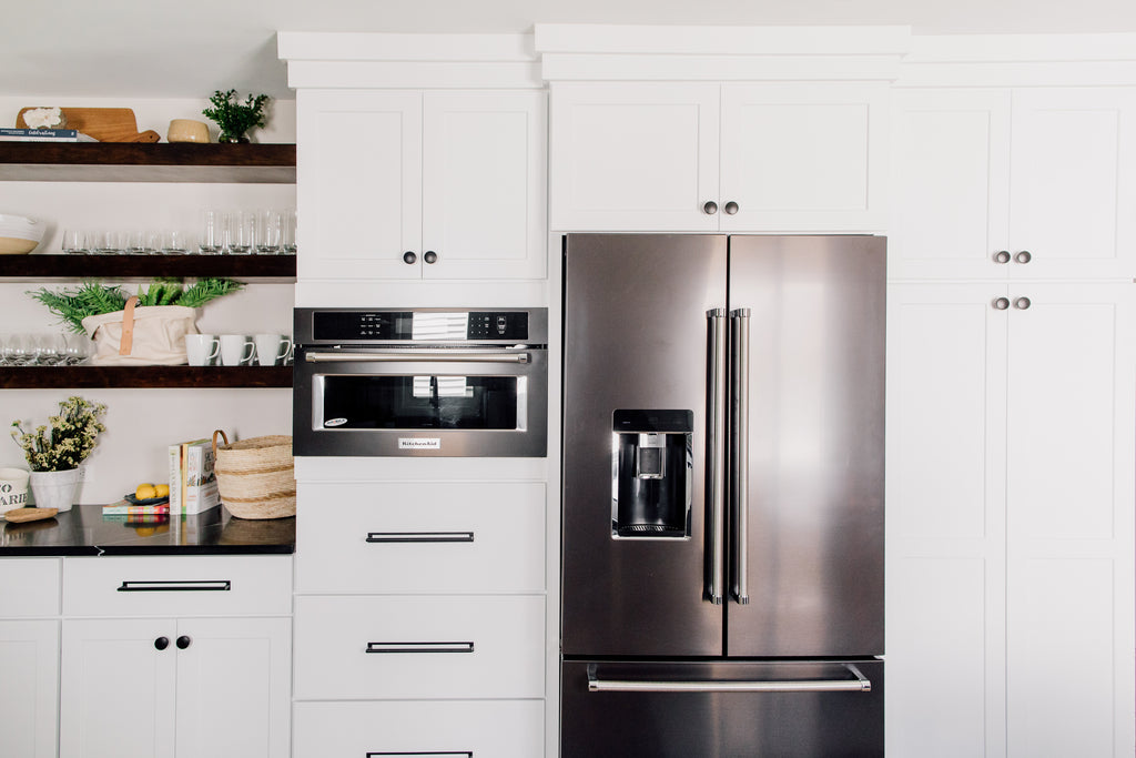 The custom-built open shelving in the kitchen is such a fun contrast to the cabinets. This is such a gorgeous way to show off cute ceramic and glassware along with seasonal decor and flowers. Love the convention KitchenAid microwave and oven black stainless steel appliances! Makes cooking so much more fun!