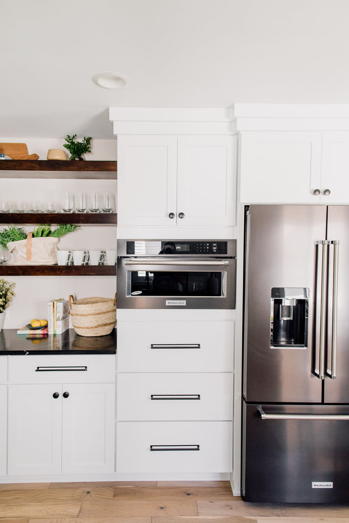 The custom-built open shelving in the kitchen is such a fun contrast to the cabinets. This is such a gorgeous way to show off cute ceramic and glassware along with seasonal decor and flowers. Love the convention KitchenAid microwave and French-door fridge in black stainless steel! Makes cooking so much more fun!