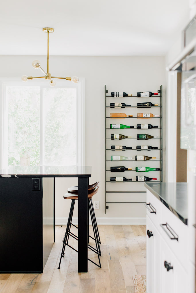The fabulous Equestrian counter stool's leather seat visually floats against the black island in a blend of utilitarian and rustic design. The Wine Rack was such a fun addition to this space, it's one of our favorite spots in the kitchen.