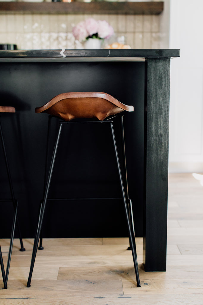 The fabulous Equestrian counter stool's leather seat visually floats against the black island in a blend of utilitarian and rustic design.