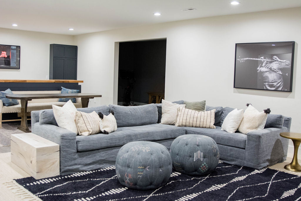 This basement features a Cisco Brothers Loft Slipcovered Sectional with black Moroccan Tulum Rug -- mixing indigo and navy and black for a masculine basement reveal!