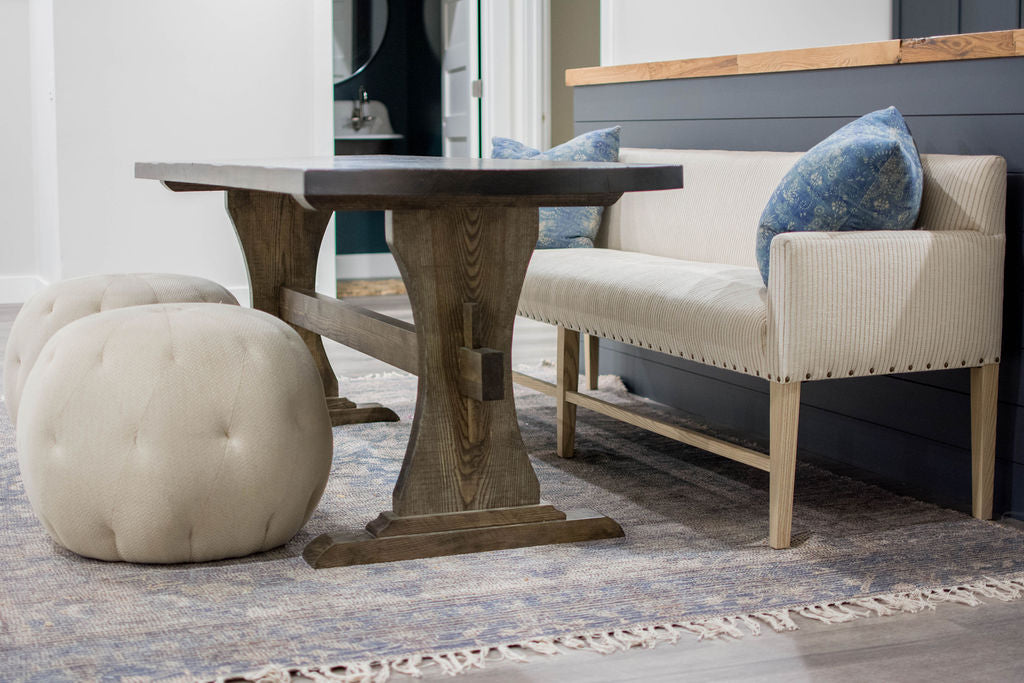 For basement dining, the client fell in love with a Verellen Thibaut dining bench paired with a handmade oval dining table, Cisco Brothers poufs, and a Loloi Cornelia rug
