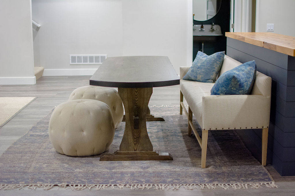 For basement dining, the client fell in love with a Verellen Thibaut dining bench paired with a handmade oval dining table, Cisco Brothers poufs, and a Loloi Cornelia rug from a different angle