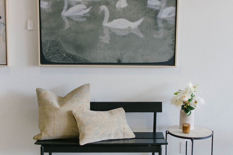 This vintage modern swan art canvas paired with a black wooden bench is the perfect backdrop.  Fresh flowers and hand-knotted pillows make for a collected, curated scene.  We are loving all things terrazzo like this side table.