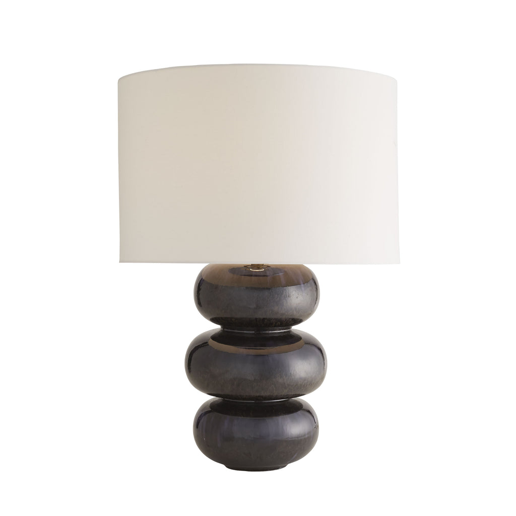 "A modern take on traditional gourd lamps, the Emanuelle Midnight Reactive Lamp showcases a multi-tiered silhouette with curves for days. A midnight reactive glaze cascades down its curvaceous porcelain form with varying deep blue and purple hues, leaving no two alike.Every descending detail is revived each time this lamp is illuminated. Topped with an off-white linen drum shade with white cotton lining. Finish may vary. Features a 3-way switch.  Size: 20""d x 28.5""h"
