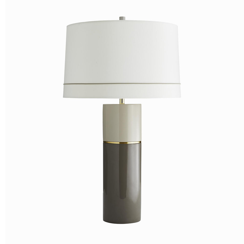 Sleek and modern in form, this piece has neutral tones and subtle details that allow it to work well in so many ways. The cylinder features two layers of bi-tonal lacquer, which are applied in the traditional -multi-layering method for a completely smooth finish. The light and dark taupe tones are separated by a thin line of inlay brass, that has a seamless weld. Topped with an off-white silk drum shade with an ivory cotton lining and cord detail to balance with the lamp design.