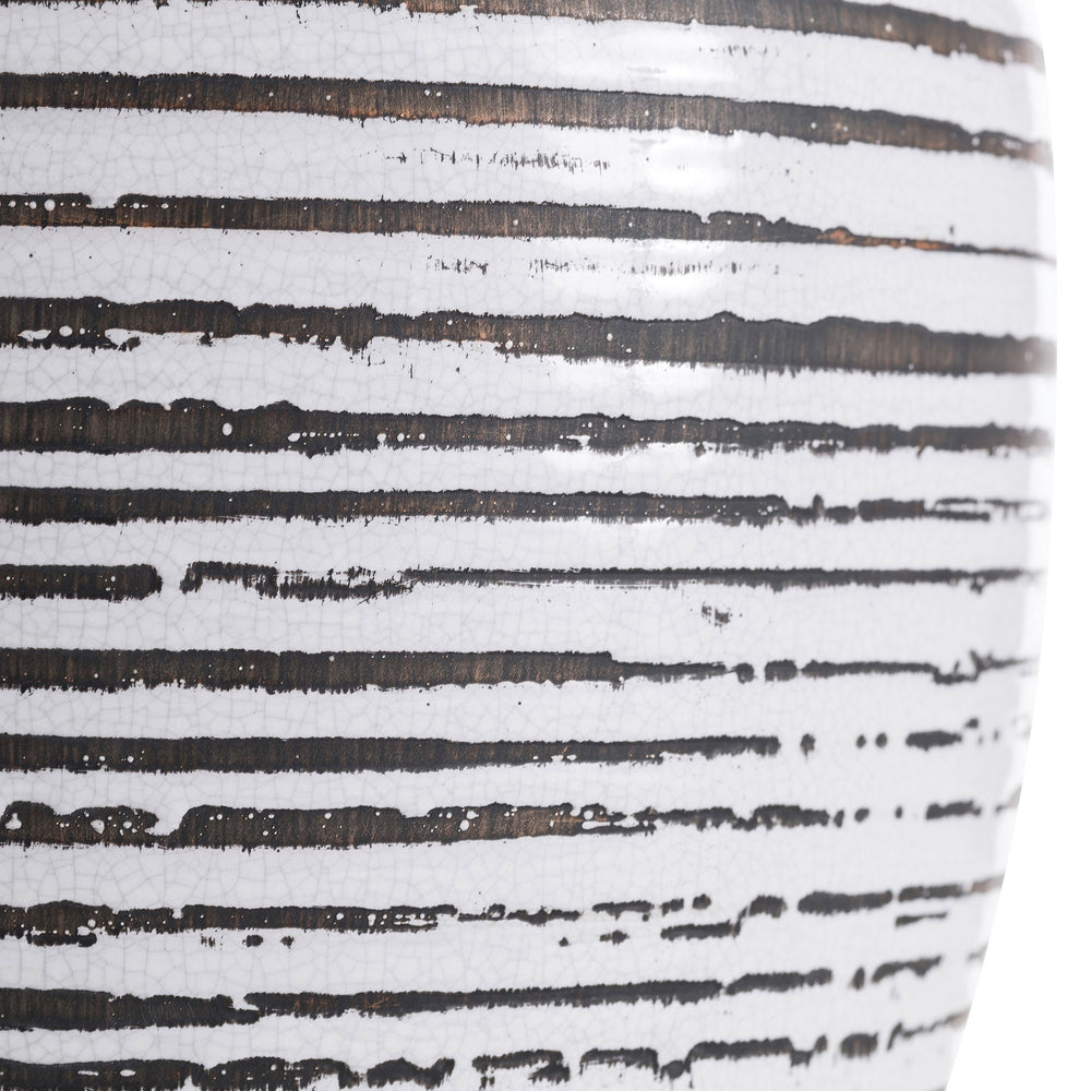 The white crackle charcoal wash finish of the ceramic Galveston Lamp creates a familiar, almost-weathered vibe. The artisan detail adds a hint of unexpectedness to an otherwise familiar, traditional form. Topped with a white microfiber drum shade and matching white crackle finial. Finish may vary.