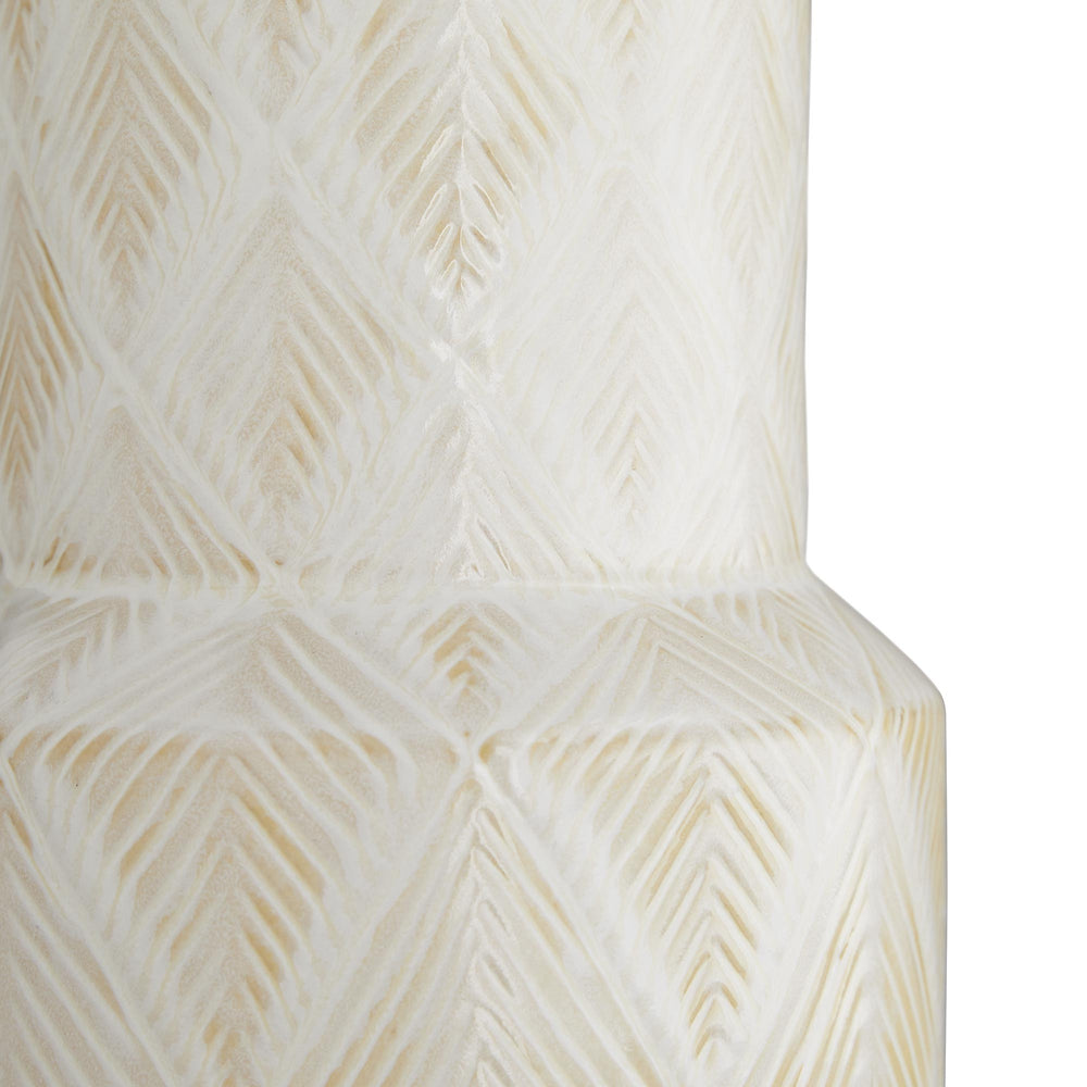 The Tory Lamp embodies artisan expression. The intricate details of the diamond leaf pattern, which have been embossed on the ceramic base, are given life when illuminated by the lamp's warm glow. A white sands reactive glaze finish has been applied, catching in the highs and lows of its textured form. Topped with an off-white linen drum shade and a matching ceramic finial. Finish may vary.