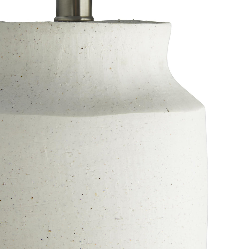 Rich in natural details, this white sand infused ceramic lamp is as artistic as it is divine. The grainy texture in the surface is from sand that's incorporated into clay before it's molded—the white tones are embedded in the clay, so the color will stay true longer. It is topped with a contrasting, slate gray linen drum shade. Finish may vary.
