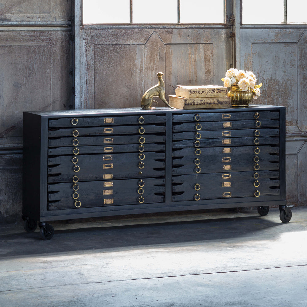 Crafted in vintage black mango wood and with brass hardware the Printmakers Console has been reconfigured to accommodate more space while retaining its classic form. There are 12 drawers for storage.