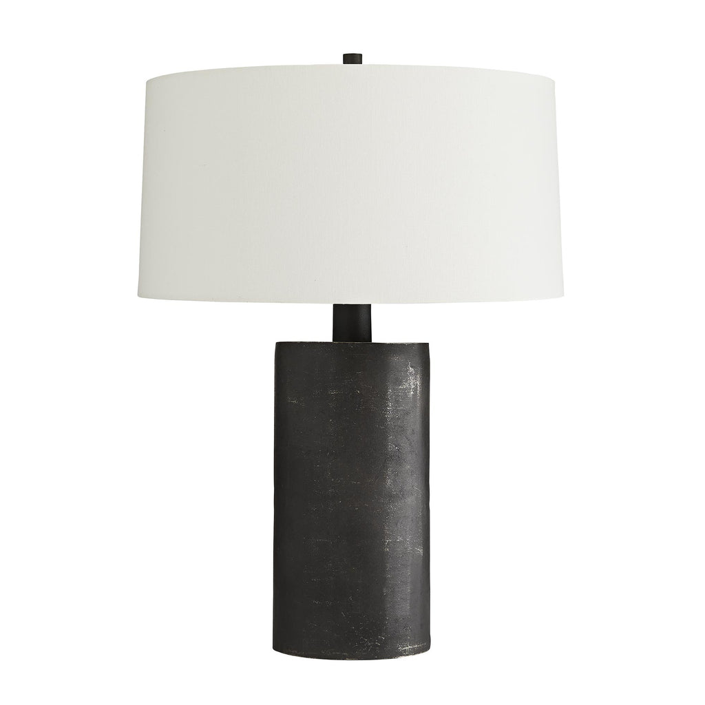 Dark and mysterious, this table lamp brings light even with its own inky hue. It's completely crafted from blackened aluminum, one of our first pieces to adorn this rich finish. The result is a sort of matte graphite look, with a bit of a raw effect, which brings out the industrial edge of this lamp. It is topped with an off-white linen drum shade with white cotton lining. Each lamp will vary due to hand-made construction.
