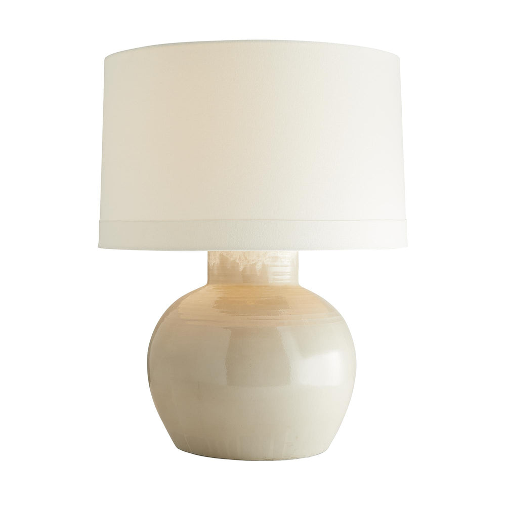 Crafted from terracotta, this lamp is formed into a wide, portly shape that makes it quite substantial, but it is balanced with a subtle, neutral Barcelona beige glaze and soft, cloudy white detail in the neck. Adding to the subtlety of detail is the delicately ridged texture at the top, which is formed by hand when the potters have wheel-thrown the base. It is topped with an ivory linen drum shade with white cotton lining. Glaze finish and details will vary.