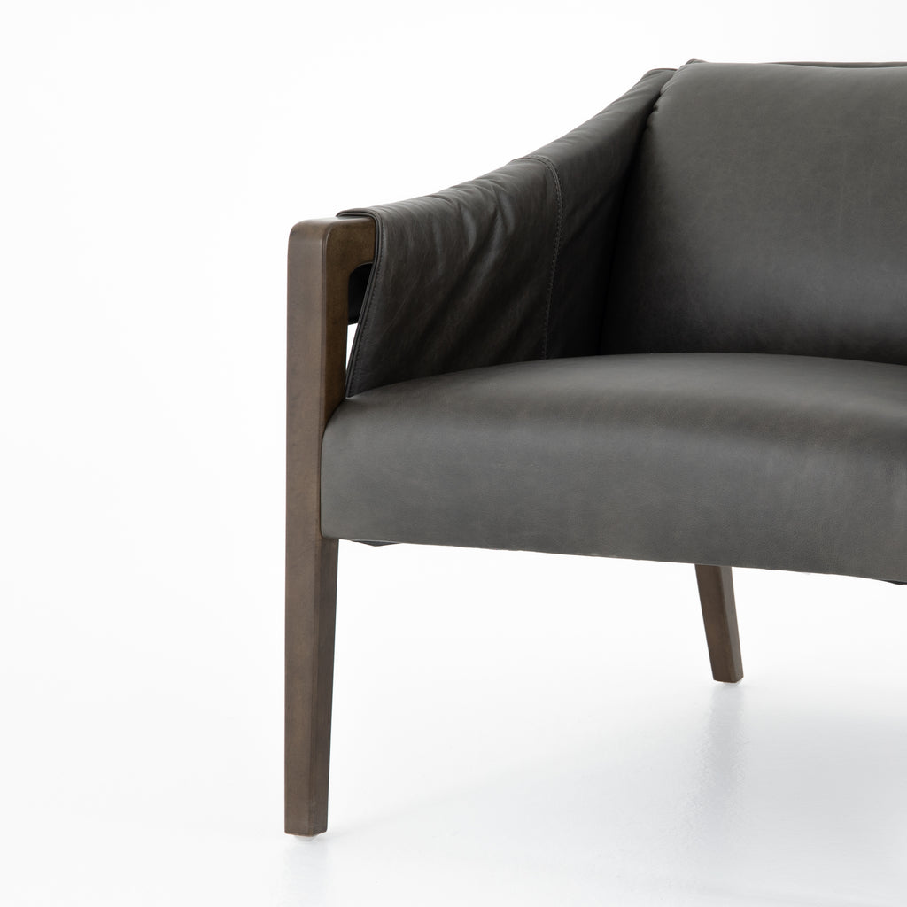 "The Bauer Ebony Leather Chair is a favorite lush seating of ebony top-grain leather that fastens to grey birch framing via trend-forward buckles. The angular arms honor mid-century design, adding a throwback feel to a cutting-edge look.  Size: 27.00""w x 35.00""d x 29.00""h"