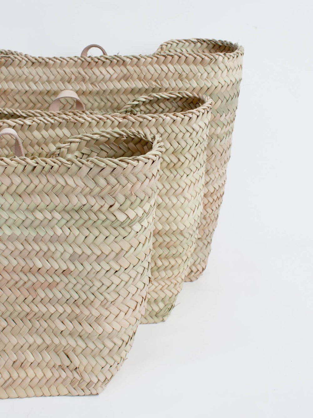 Our Moroccan hanging wall basket is handwoven from palm leaf and finished with a natural leather loop as the perfect indoor planter or storage solution.