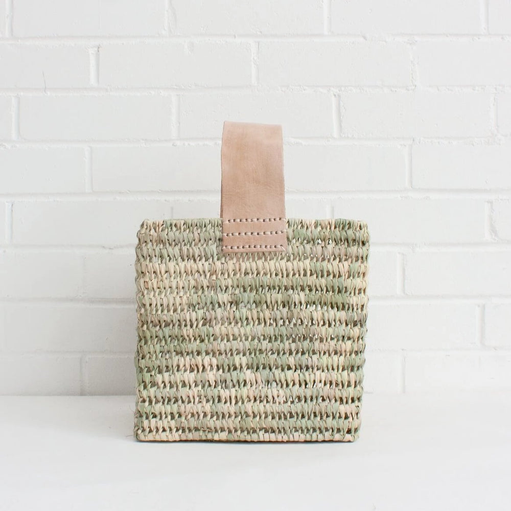 The Tall Forage Basket is handwoven in Morocco using palm leaf in a sturdy open weave with a soft natural leather handle. A modern design, the rectangle basket is perfect for shopping trips or as decorative storage around the home.