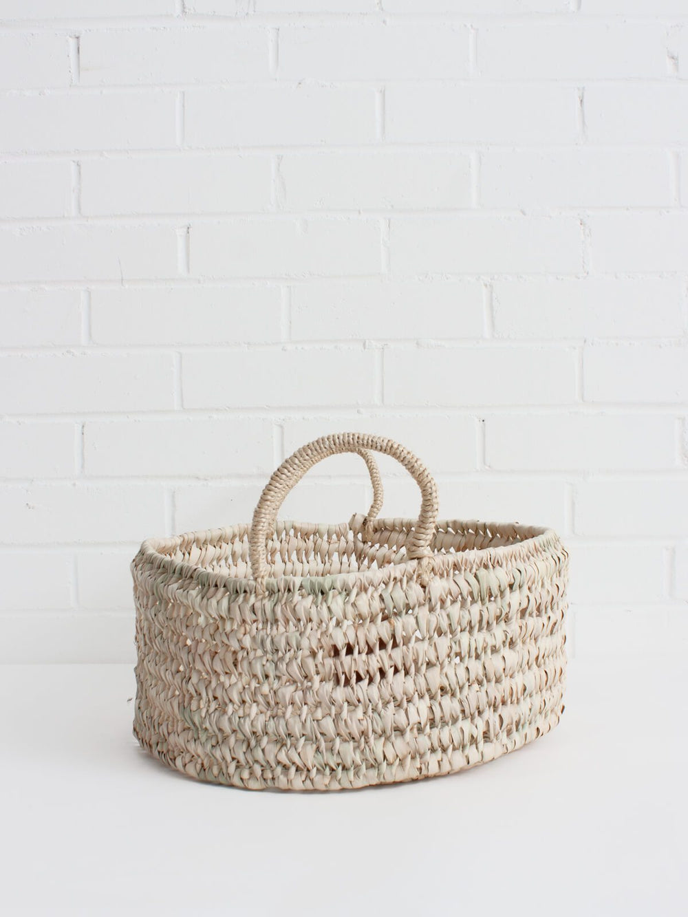 The Large Round Storage Basket is handwoven in Moroccan in a robust open weave using sustainable palm leaf and can be used as fruit bowls, bread baskets or an ideal home storage solution.