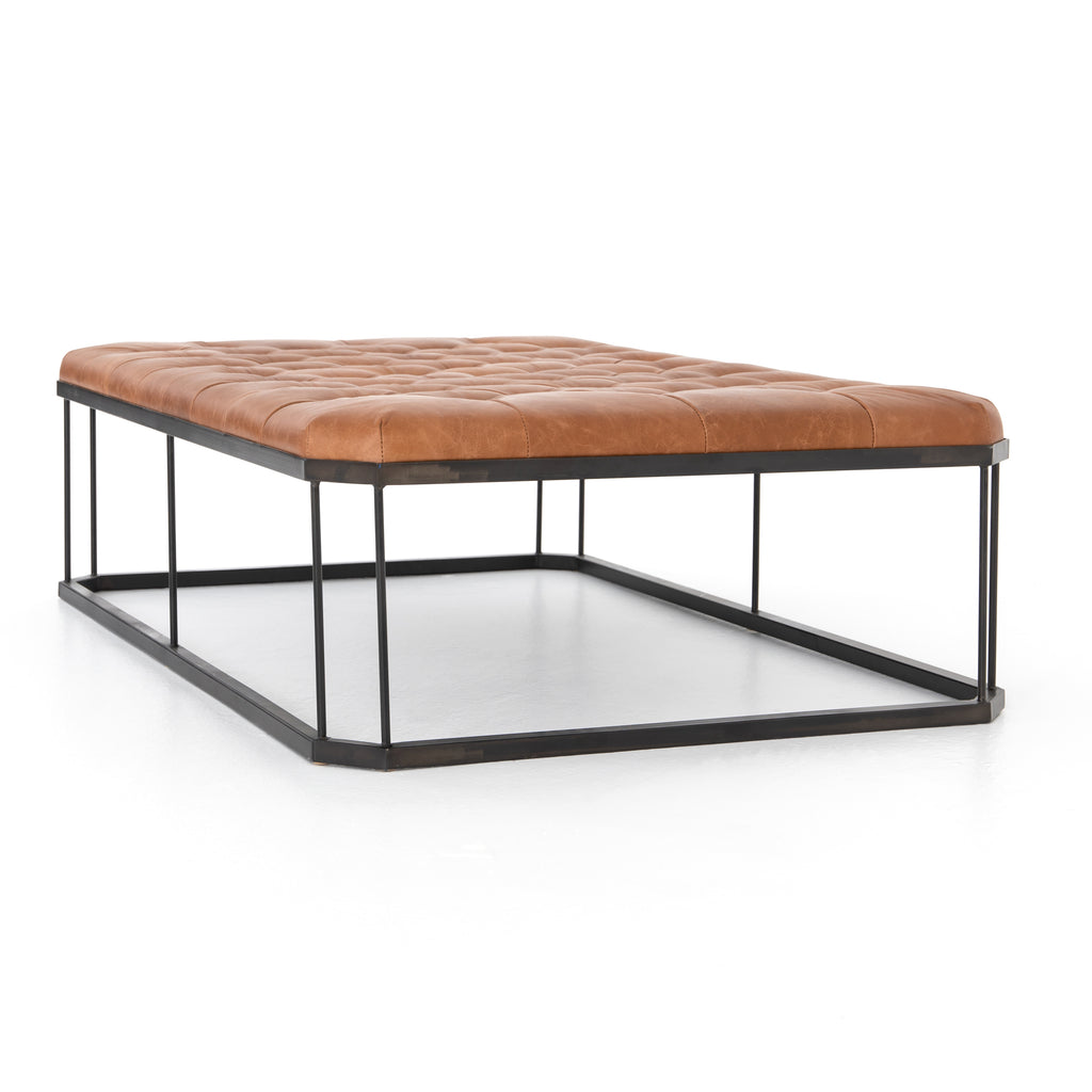 "A new take on the ottoman, the Isle Ottoman intrigues with leather in dramatic diamond-tufting, angled corners and open iron base. Great as a coffee table, too.  Size:  53.25""w x 35.75""d x 15.75""h"