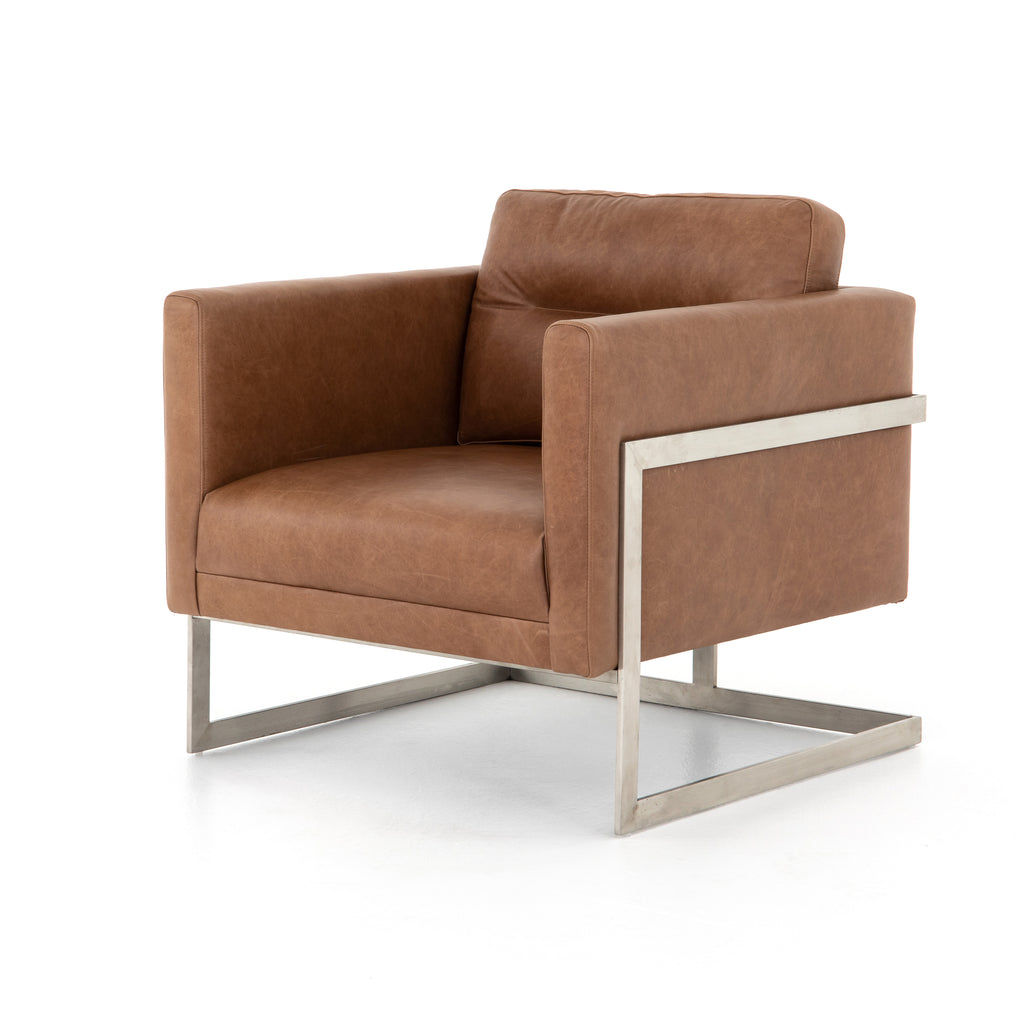 "The Fiona Chaps Saddle Chair is shape-driven seating. An upholstered cube of tan top-grain leather appears to float within an angular flat-bar frame of brushed silver. Horizontal tufting for texture, back cushion for comfort.  Size: 30""w x 32""d x 30.5""h Seat Depth: 21"" Seat Height: 18"" Materials: Top Grain Leather, Stainless Steel"