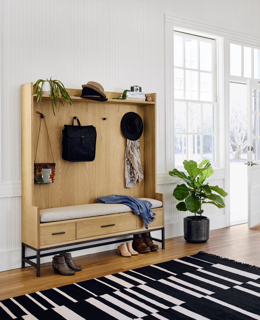 Bring order to the bustling entryway with this stately bench-style hutch. Contrasting a black iron base, a high-back bench of natural oak features four iron hooks for hanging hats, jackets and handbags. Three drawers for hidden storage and linen-blend cushion for comfort.