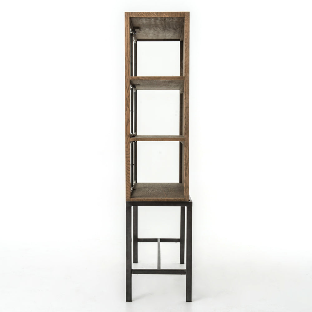 "We love how the Spencer Drifted Oak Curio Cabinet is perched on a simple, waxed black iron pedestal. The drifted oak forms an airy curio cabinet designed to highlight life's artifacts. Overall Dimensions: 45.75""w x 16""d x 69""h Materials: Iron, Glass, Reclaimed Oak"
