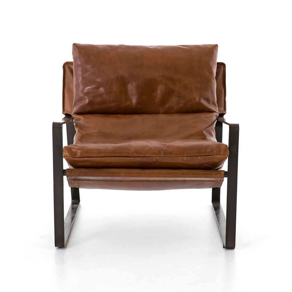 Super stylish, effortlessly cool. Sling-style seating of tobacco-toned leather sits low and curved for a fresh take on a throwback form. Slim, gunmetal-finished iron framing ups the drama factor of an innately hip design.