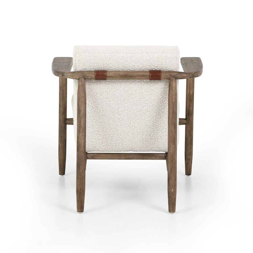 Textural cream bouclé seating offers a sumptuous sit, with complementary wire-brushed parawood framing forming a slim U shape. Two posterior top-grain leather straps add a stylish finishing touch.
