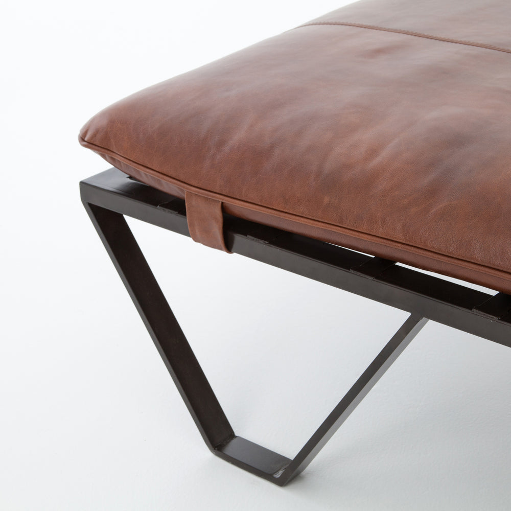 The ottoman, re-invented. Cunningly shaped and distressed, flatstock iron supports a spare-yet-comfortable cushion in aged, top-grain leather.