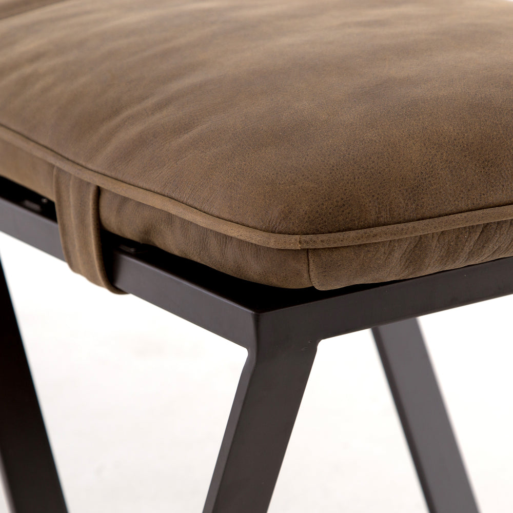 The ottoman, re-invented. Cunningly shaped and distressed, flatstock iron supports a spare-yet-comfortable tan cushion in aged, top-grain leather.