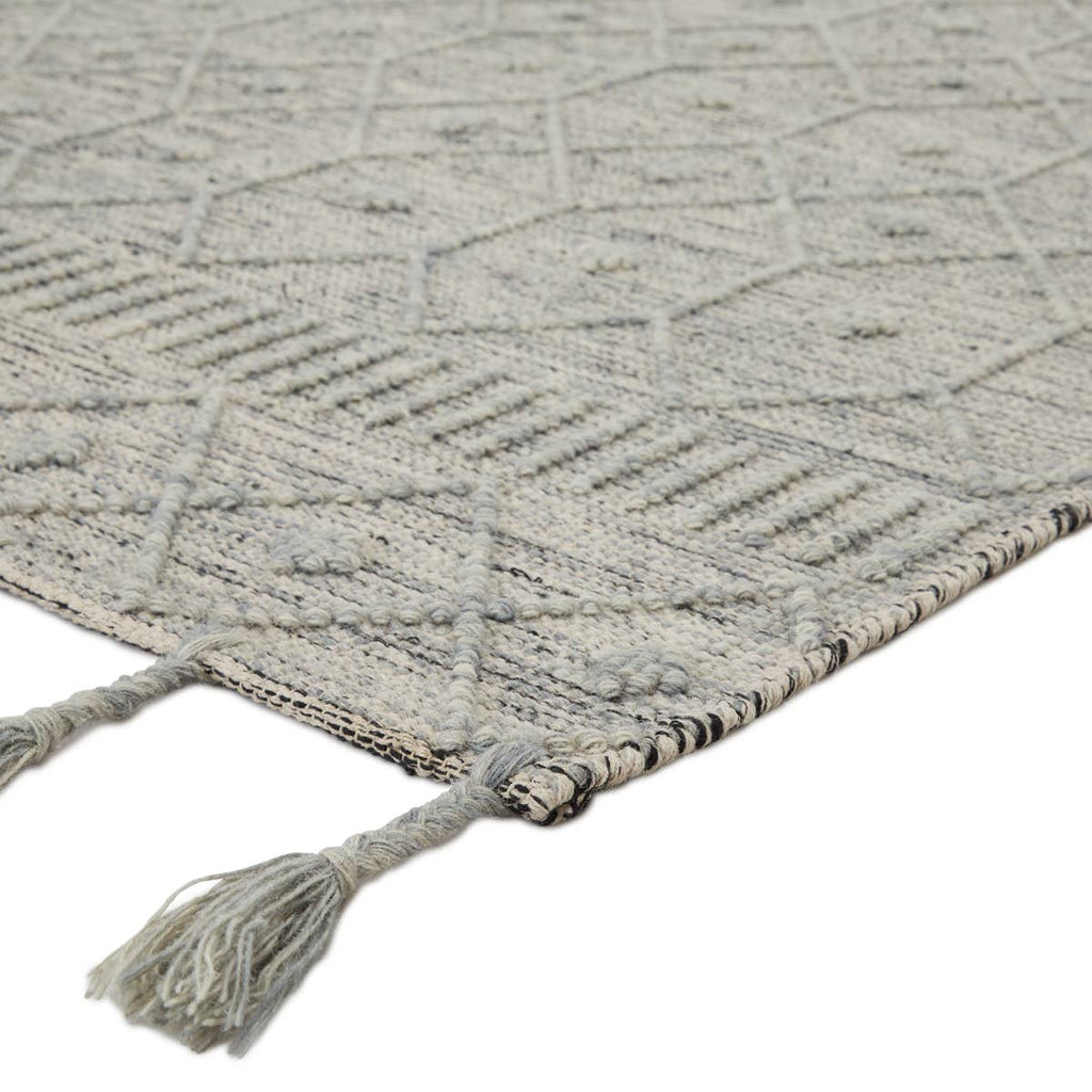 The Calixta Anza Area Rug by Jaipur Living, or CAX01, features a cool blue-gray colorway with interwoven yarns of black and cream for added dimension. The raised boucle lattice motif and braided fringe details lend a global vibe to this handcrafted rug. A beautiful rug for the entry way or other high traffic area.