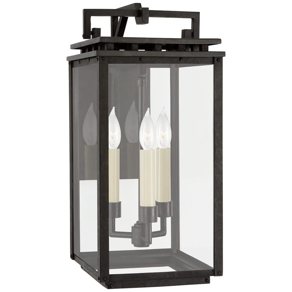 The details are everything in this Cheshire Aged Iron Small Bracketed Wall Lantern.  The top portion has gorgeous, geometrically appealing cut outs while the three candles inside give it a timeless look  Designer: Chapman & Myers