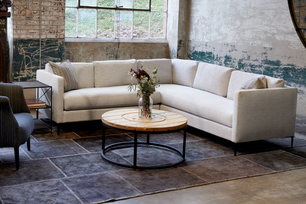 "The Benedict 2 Arm Sectional - Essentials by Cisco Brothers is a modern design with clean lines and sleek metal legs in black rust. It has a fresh and functional aesthetic with no-sag support. Photographed in Vanocur Natural and Navedo Gravel.  Overall: 96""w x 96""d x 29""h"