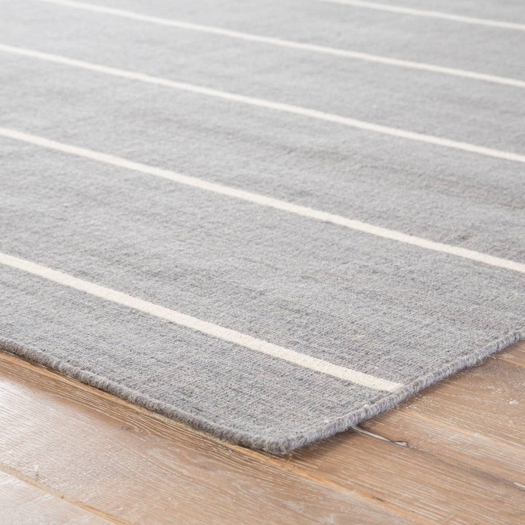 Classic with a bold stripe, this Coastal Shores Cap Cod Area Rug, or COH13, has wheathered gray and bright white flatweave. The area rug lends traditional charm to any space. This casual layer offers reversible use for easy care and timeless durability. Flat Weave 100% Wool.