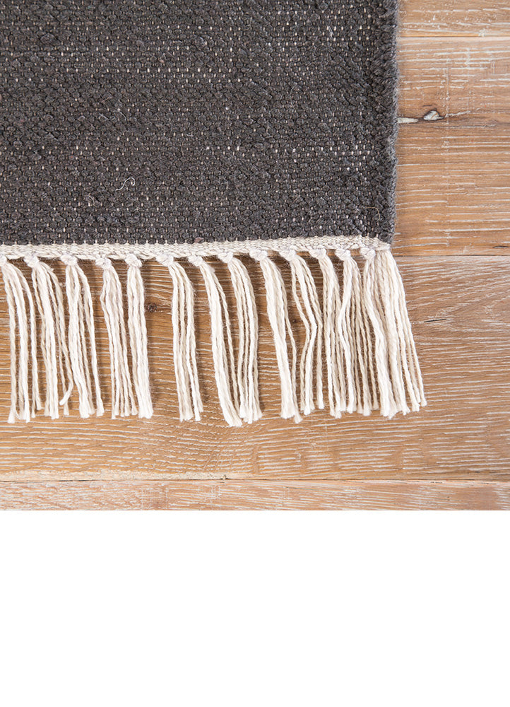 The Desert Swane area rug introduces a classic Southwestern style to modern homes. Constructed of weather-resistant polyester, this hand-loomed flatweave boasts incredible durability for both indoor and outdoor use. The bold stripe design showcases a neutral gray, gold, and white colorway, accented with knotted fringe for added texture and charm.  Indoor/Outdoor 100% Polyester DES18