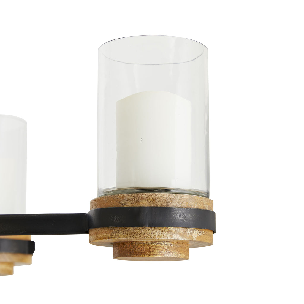 "The five arm Sumter Candle Chandelier is elemental and graphic in shape, mingling natural wood, clear glass cylinders, iron arms and wood-inset details. The pared down silhouette is aesthetically versatile and could reside in a country farmhouse oran urban minimal apartment. Ivory resin candle sleeves lends a certain romanticism to the piece. Damp-rated, although limited covered outdoor conditions may affect finish.  Size: 33""d x 10.5""h"