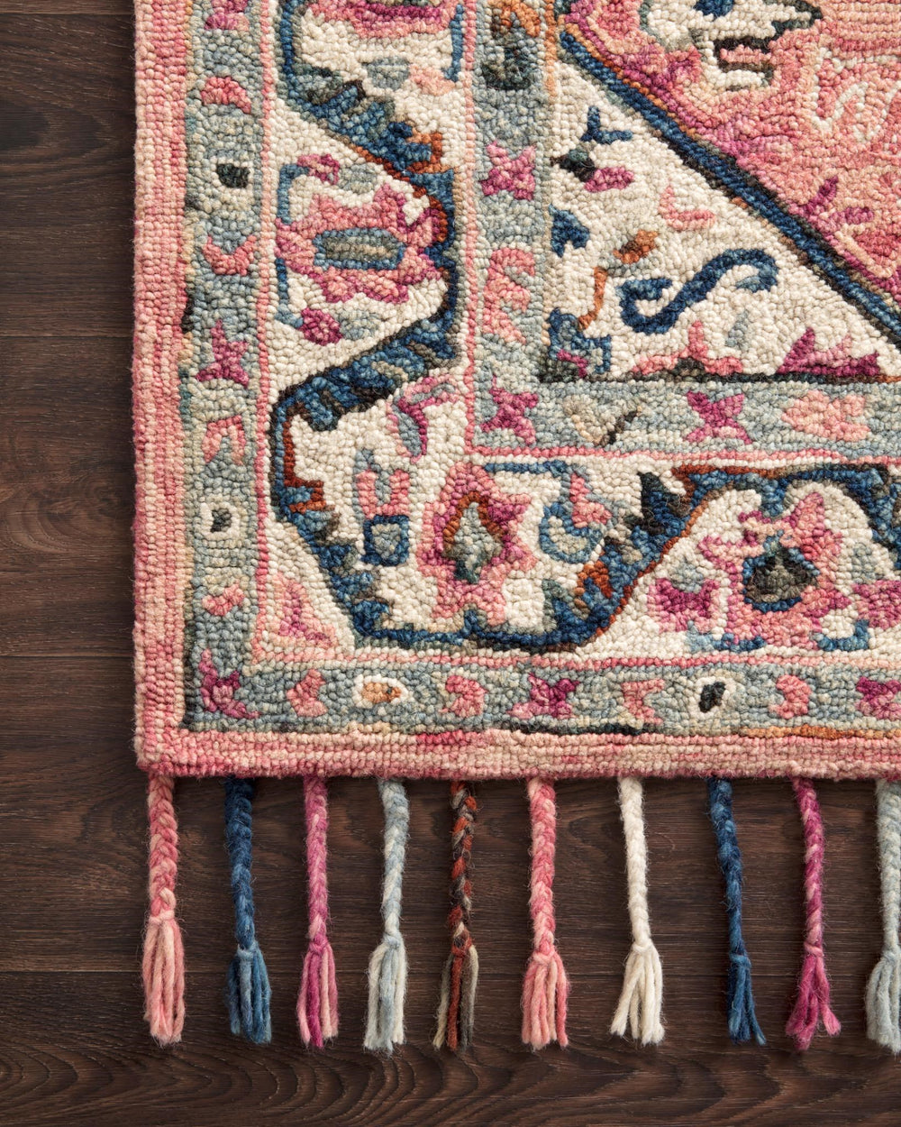 Hooked of 100% wool by skilled artisans in India, this collection of transitional rugs is soft to the touch and displays whimsical floral motifs complemented by luxurious, braided tassels to perfectly complement any space.  Hooked 100% Wool ELK-04 Pink/Multi