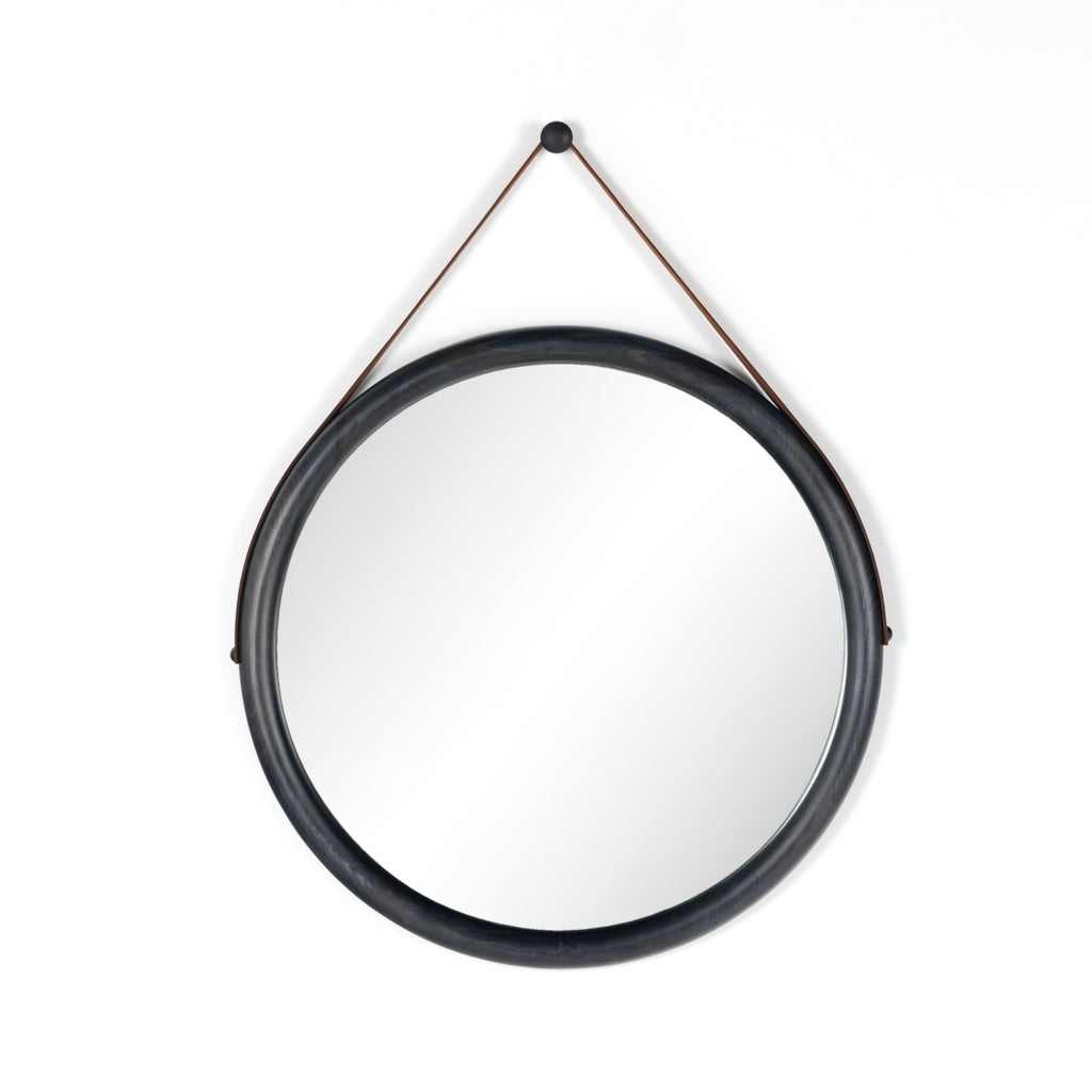 "The Des Mirror is hung by a handsome, toffee-colored top grain leather strap. We love the fresh take on what would otherwise be a traditional, round mirror. The mirror is framed in black-washed popular and would like amazing hung in an entryway, bedroom, or other space.   Overall Dimensions: 30.00""w x 1.50""d x 30.00""h Colors: Natural Iron, Black Wash Poplar, Toffee Leather Materials: Iron, Solid Poplar, Top Grain Leather  Please allow 3-4 weeks on shipment for these items."
