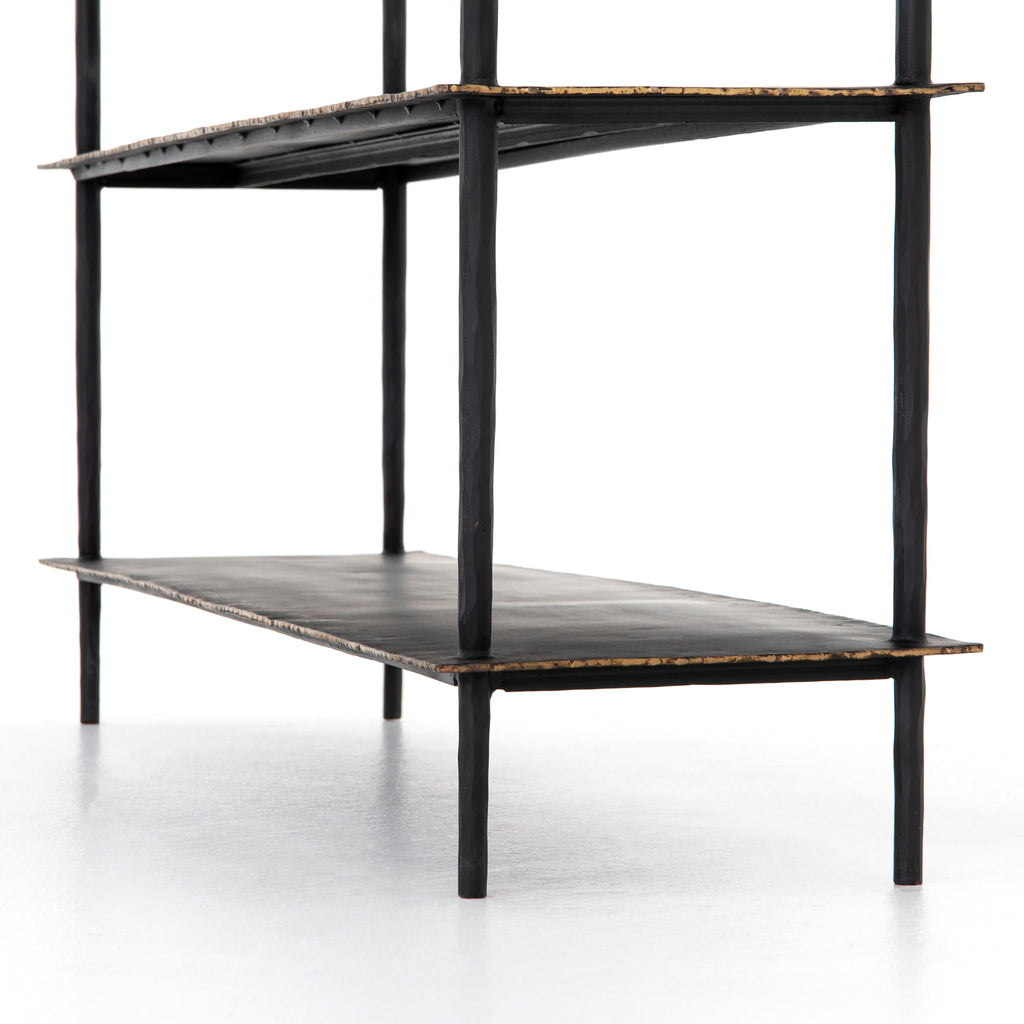 A rubbed black finish brings an industrial sense to open-air console storage in the Trula Console Table. Three wide iron slabs stack, bring a clean, tiered look and ample space for console storage and display.