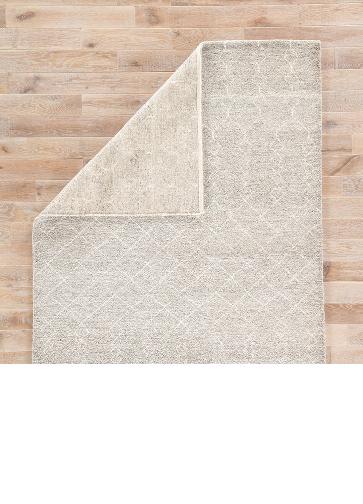 Rich in detail and plush underfoot, the Indira collection is made up of neutral-toned modern Moroccan styles. The Margo area rug features a luxurious hand-knotted construction of natural wool and tencel. A white diamond trellis design provides geometric interest to a soft gray backdrop. Scalloped edges add a unique accent to this high-piled rug.  Hand-Knotted 95% Wool, 5% Tencel IND02